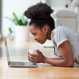 Woman on floor with cup looking at laptop