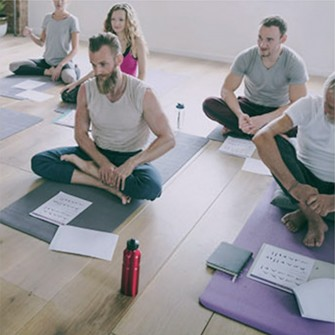 Man sitting on mat in yoga class