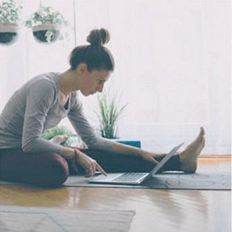 Woman using laptop and doing yoga